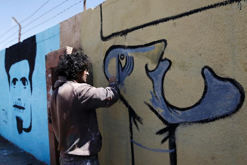 A man works on a mural on the southern wall of Sanaa University during the Open Day of Art event