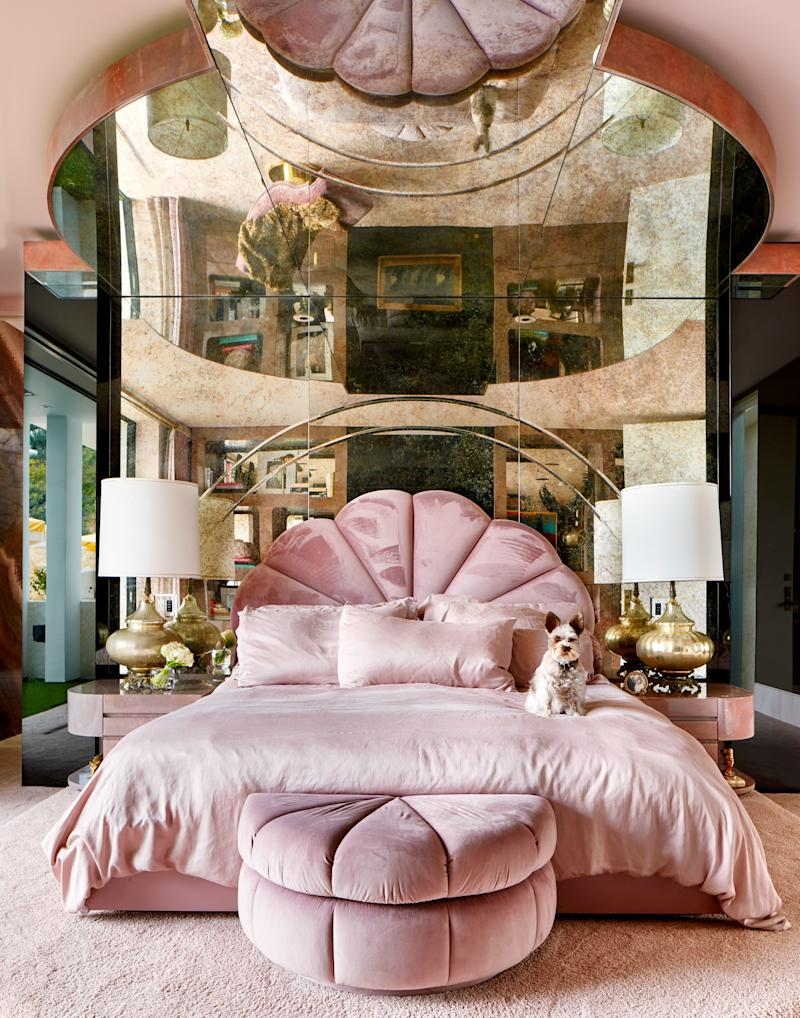 The master bedroom channels 1970s opulence with a custom-made seashell bed upholstered in mauve velvet, underneath a ceiling of smoked mirrors. The side tables and satin bedding are custom made, and the Moroccan lampshades are vintage.