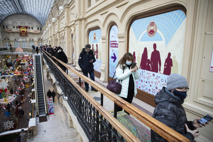 People stand in a queue to get a shot of Russia's Sputnik V coronavirus vaccine in a vaccination center in GUM State Department store in Moscow, Russia, Wednesday, Jan. 20, 2021. Russia started a mass coronavirus vaccination campaign on Monday, Jan. 18. (AP Photo/Pavel Golovkin)