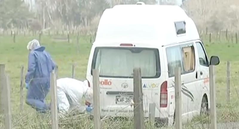 Police officers inspect an Apollo campervan stopped on the side of the road at Waikato.