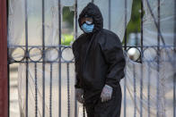 A funeral home worker wearing a full protective gear to protect himself from the spread of the new coronavirus waits to enter La Verbena cemetery in Guatemala City, Tuesday, July 28, 2020. (AP Photo/Moises Castillo)