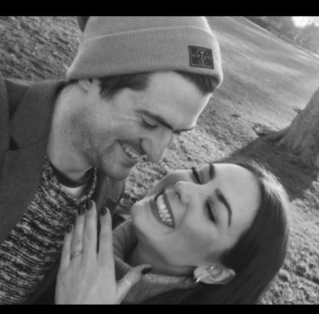 A man and woman pose for a selfie. The man (left) is wearing a beanie hat and looking at his fiance (right) who is holding her hand up to the camera