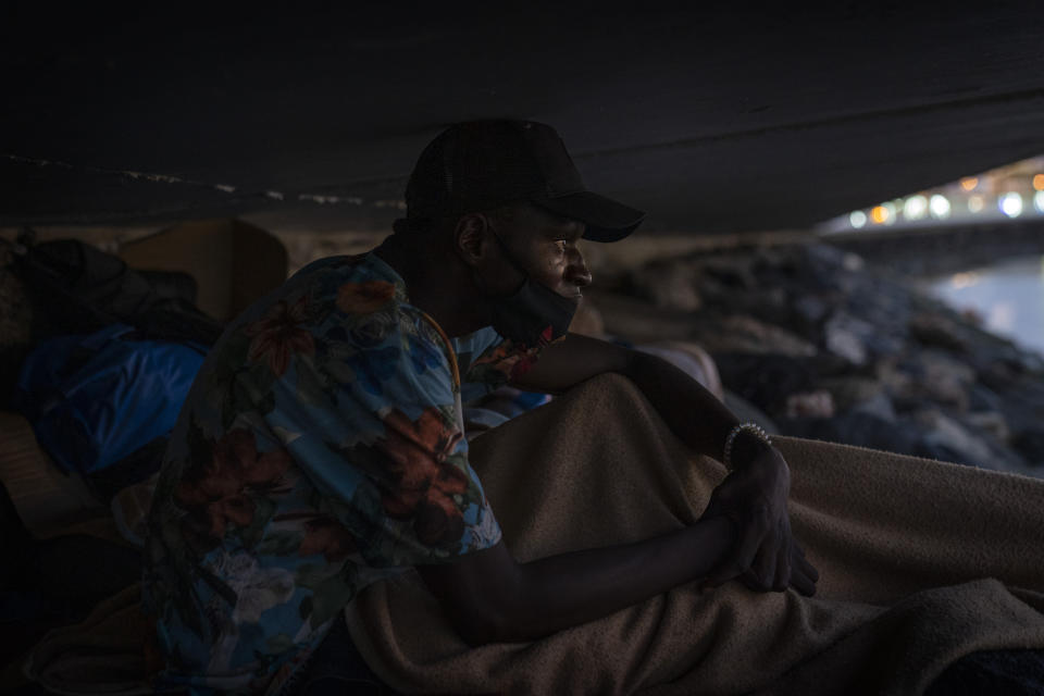Khalid, a migrant from Gambia, sits on a breakwater under a bridge in Gran Canaria island, Spain, on Saturday, Aug. 22, 2020. More than 250 people are known to have died or gone missing in the Atlantic route so far this year according to the International Organization for Migration. That's already more than the number of people who perished trying to cross the Western Mediterranean in all of last year. (AP Photo/Emilio Morenatti)