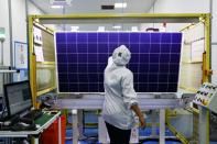 FILE PHOTO: Employees work on a solar energy panel of Chinese solar equipment manufacturer BYD in Campinas