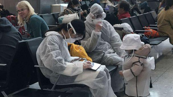 PHOTO: A group of travellers wear protective clothing in the departure lounge at Heathrow Airport Terminal 2 in London, March 19, 2020. (Carina Ferreira/Reuters)