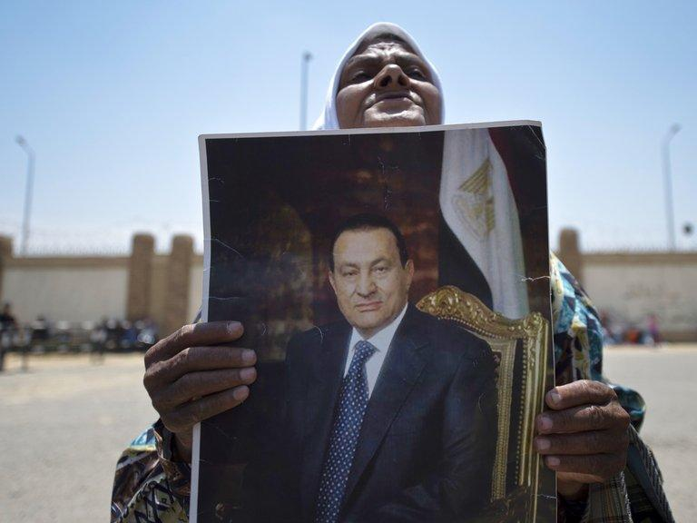 "A supporter of former Egyptian president Hosni Mubarak, holds a portrait of him outside the Egyptian police academy in Cairo, where his trial is taking place, May 11, 2013. Mubarak, on trial for the death of protesters during Egypt's 2011 uprising that toppled him, said future generations would judge him ""fairly"" in an interview published on Sunday"