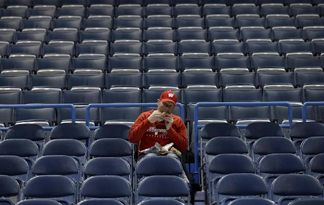 A lone fan eats his hotdog in the stands before a second-round game in the NCAA college basketball tournament between the Wisconsin and the American Thursday, March 20, 2014, in Milwaukee. (AP Photo/Jeffrey Phelps)