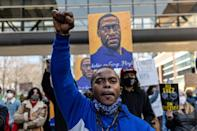 Demonstrators hold signs honouring George Floyd outside Hennepin County Court in Minneapolis, Minnesota