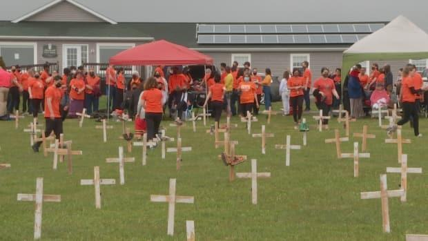 People gather near small crosses erected at the Abegweit First Nation in Scotchfort, P.E.I., to honour the victims of the Kamloops Indian Residential School.