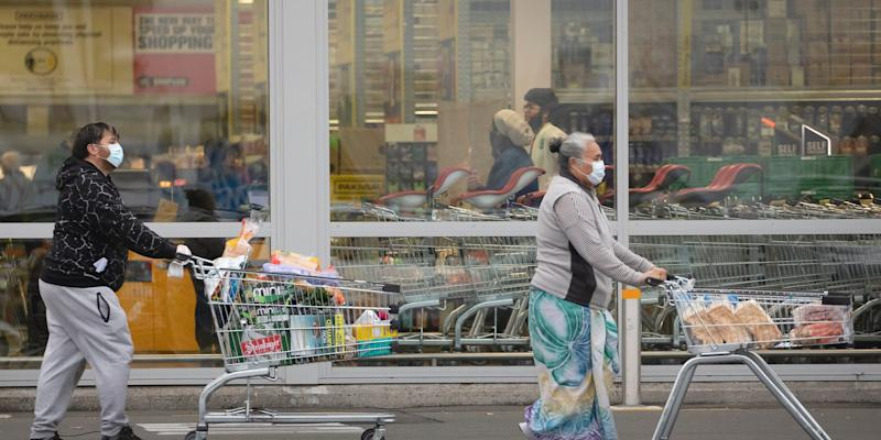 People wearing face masks, push shopping cart with their grocery items in Christchurch, New Zealand, on April 01.
