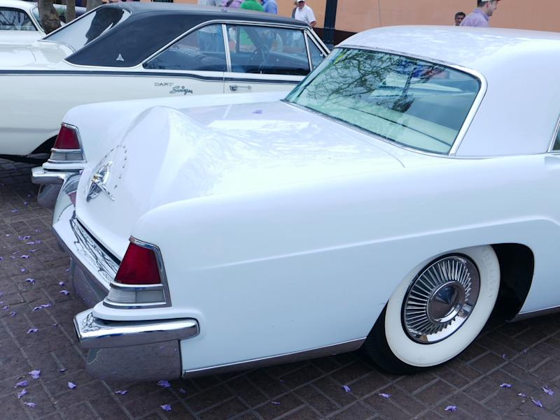 Lima, Peru. December 4, 2016. Rear view of a white color mint condition second generation of Lincoln Continental Mark II coupe built between 1956 and 1958 in the USA by Ford Motor Company. The car is powered by a V8 engine. It was exhibited in a vintage cars show meeting in Pueblo Libre district of Lima. Incidental persons are in the image. This photo was taken by a Leica camera on a sunny day.