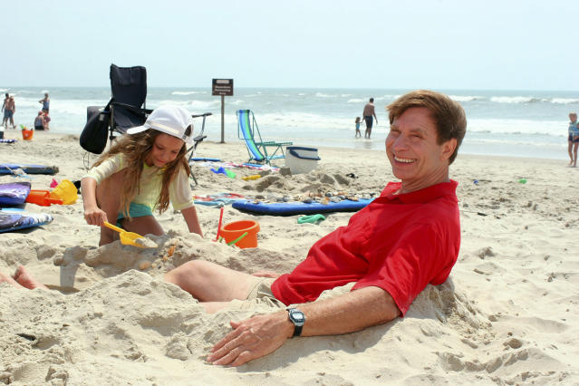 """FILE - In this June 8, 2007, file photo, Dr. Stephen Leatherman, aka """"Dr. Beach,"""" poses on the beach at Ocracoke, N.C., as Mara Chemerinsky, 8, a visitor from Durham, N.C., plays in the sand. Since 1991, Leatherman has compiled an annual list of America's best beaches, making sand and surf a science and earning the nickname """"Dr. Beach."""" His latest list will be released Thursday, May 23, 2019. (AP Photo/Mary Haggerty, File)"""