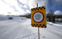 FILE - In this Jan. 28, 2021 file photo, a sign marks the closed ski slope in Cortina D'Ampezzo , Italy. On the eve of what was supposed to finally be the repeatedly delayed opening of Italy's ski slopes, the government on Sunday, Feb. 14, 2021, yanked permission because a coronavirus variant was found to be circulating in a good portion of recently infected persons. Health Minister Roberto Speranza's ordinance forbids amateur skiing at least until March 5. (AP Photo/Antonio Calanni)