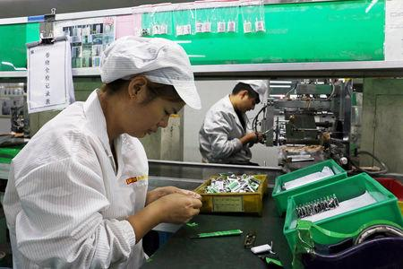 FILE PHOTO:    Employees work at a production line of lithium ion batteries inside a factory in Dongguan, Guangdong province, China October 16, 2018. Picture taken October 16, 2018. REUTERS/Joyce Zhou/File Photo