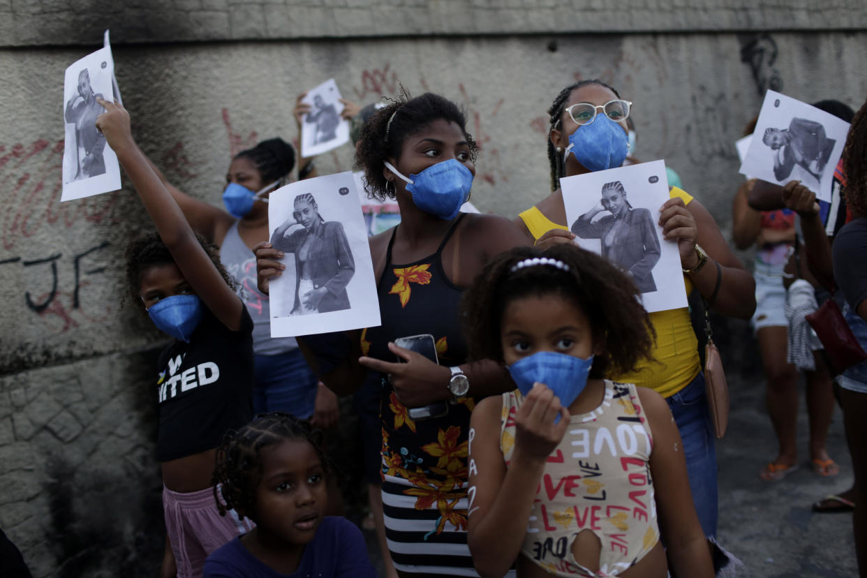 Residents carry flyers with the image of Kathlen Romeu, a young pregnant woman killed by a stray bullet, in Rio de Janeiro, Brazil, Wednesday, June 9, 2021. Stray bullets have struck at least six pregnant women in Rio since 2017, but Romeu was the first to die, according to Crossfire, a non-governmental data project that tracks armed violence. (AP Photo/Bruna Prado)