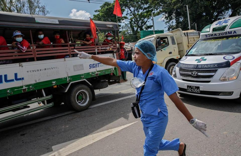 A health worker tries to make way for an ambulance to pass through an election campaign rally in Yangon, Myanmar, on 25 October 2020.