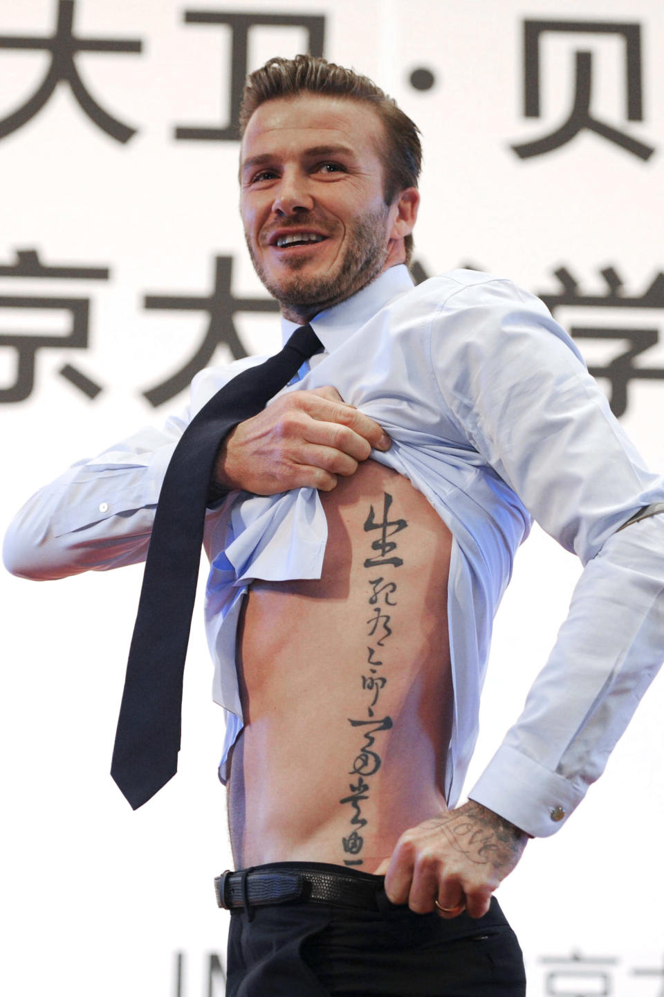 <p>David Beckham reportedly has over 50 tattoos, including one of his daughter Harper's name on his neck and the number 99 on his wrist – the year he wed wife Victoria Beckham. Here, you can see the former footballer's side tattoo which bears the words: 'Death and life have determined appointments, riches and honour depend upon heaven' in Chinese. <em>[Photo: Getty]</em> </p>