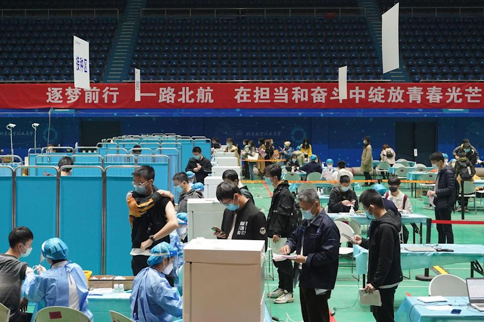 Residents line up to get vaccinated at Beihang University in Beijing. Photo: Xinhua