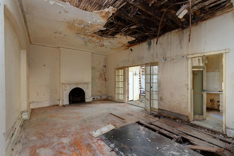 Inside of a rundown Darlinghurst home in Sydney is pictured with the ceiling caving in and floorboards ripped up.