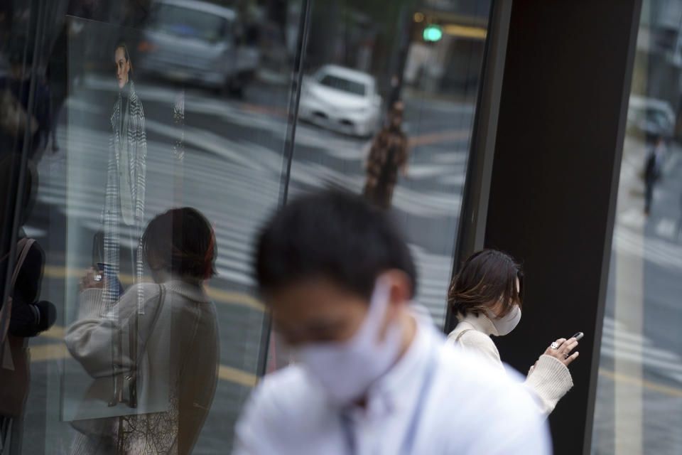 People wearing protective masks to help curb the spread of the coronavirus pause near a shopping building Wednesday, Nov. 25, 2020, in Tokyo. The Japanese capital confirmed more than 400 new coronavirus cases on Wednesday. (AP Photo/Eugene Hoshiko)