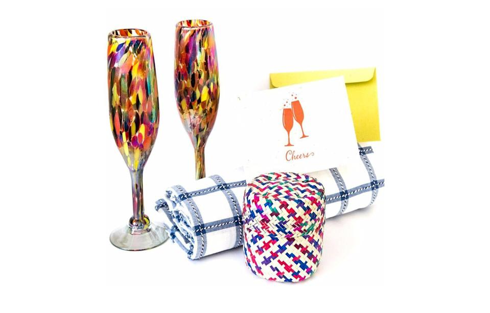 """<p> Give mom something to celebrate! The Cheers Box from GlobeIn includes a set of handmade glass champagne flutes, a table cloth, and a cute card. </p><p><a class=""""link rapid-noclick-resp"""" href=""""https://go.redirectingat.com?id=74968X1596630&url=https%3A%2F%2Fshop.globein.com%2Fcollections%2Fartisan-boxes%2Fproducts%2Fcheers-box&sref=https%3A%2F%2Fwww.countryliving.com%2Fshopping%2Fgifts%2Fg19663932%2Fmothers-day-gift-baskets%2F"""" rel=""""nofollow noopener"""" target=""""_blank"""" data-ylk=""""slk:SHOP NOW"""">SHOP NOW</a></p>"""
