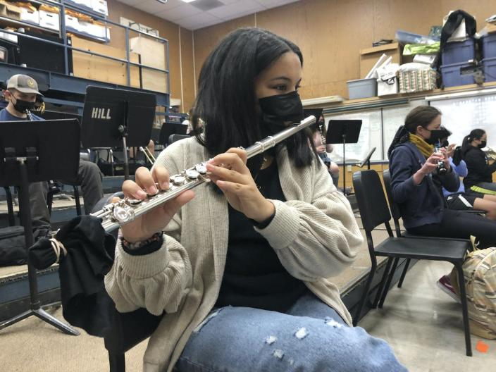 A student plays a flute through a mask during band practice.