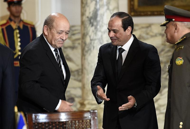 French Defence Minister Jean-Yves Le Drian (L) and Egyptian President Abdel Fattah al-Sisi (R) arrive for the signing of a contract for Rafale fighter jets on February 16, 2015 at the presidential palace in Cairo