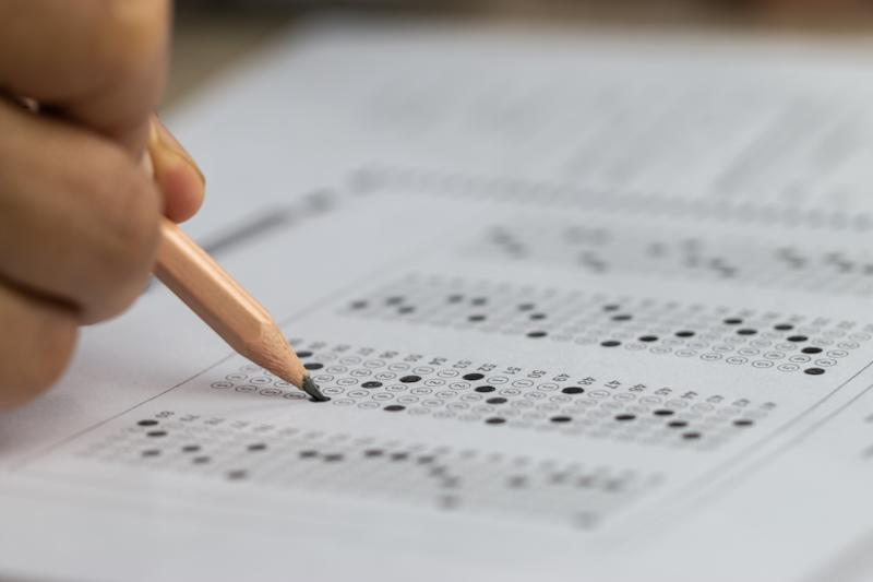 Hand of student holding pencil for exam