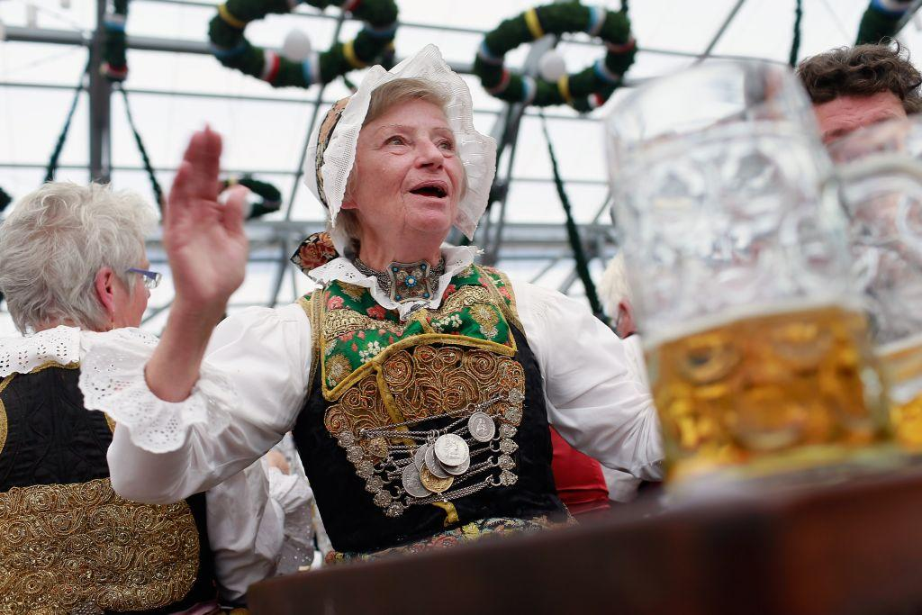 A woman from Lower Bavaria, dressed in ceremonial Bavarian costume, enjoys a beer after participating in the opening parade. The 16-day festival runs till October 7.