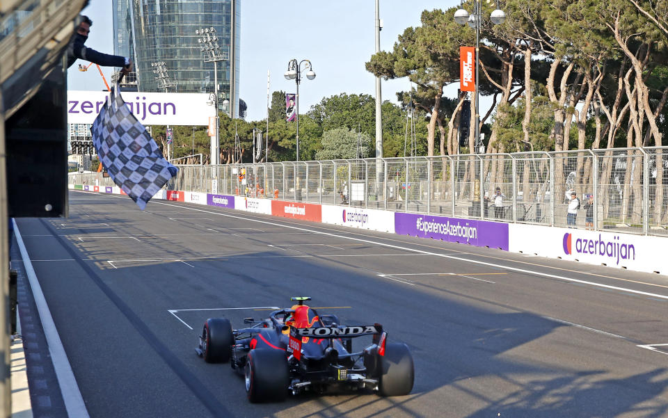 The checkered flag waves for Red Bull driver Sergio Perez of Mexico as he crosses the finish line to win the Formula One Grand Prix at the Baku Formula One city circuit in Baku, Azerbaijan, Sunday, June 6, 2021. (Maxim Shemetov, Pool via AP)