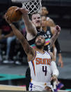Phoenix Suns guard Jevon Carter (4) is blocked by San Antonio Spurs center Jakob Poeltl (25) as he tries to score during the first half of an NBA basketball game in San Antonio, Sunday, May 16, 2021. (AP Photo/Eric Gay)