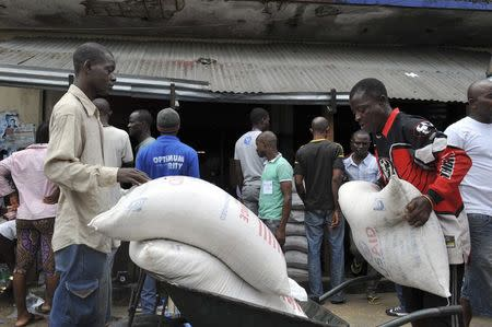 Residents of West Point neighborhood, which has been quarantined following an outbreak of Ebola, receive food rations from the United Nations World Food Programme (WFP) in Monrovia August 28, 2014. REUTERS/2Tango