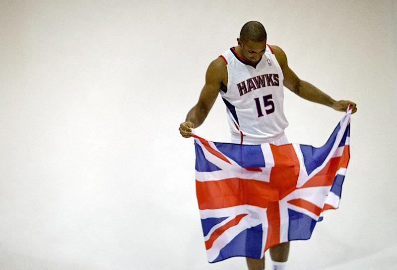 Atlanta Hawks' Al Horford holds a British flag given to him by a photographer before posing for a photo during their NBA basketball media day, Monday, Sept. 30, 2013, in Atlanta. The flag references the team's trip to London in January to face the Brooklyn Nets. (AP Photo/David Goldman)