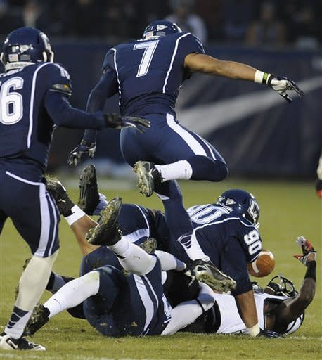 Connecticut defense causes Cincinnati wide receiver Kenbrell Thompkins (7) to fumble the ball during the first half of an NCAA college football game at Rentschler Field in East Hartford, Conn., Saturday, Dec. 1, 2012. (AP Photo/Jessica Hill)