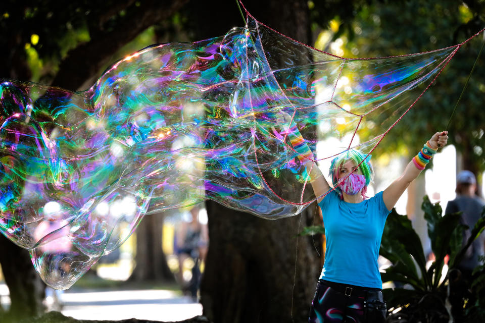 A woman plays with giant soap bubbles on August 15, 2021 in Singapore. (Photo by Suhaimi Abdullah/NurPhoto via Getty Images)