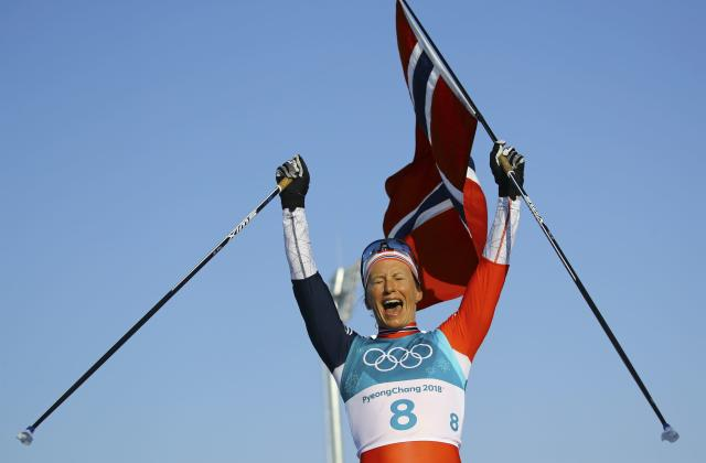 Cross-Country Skiing - Pyeongchang 2018 Winter Olympics - Women's 30km Mass Start Classic - Alpensia Cross-Country Skiing Centre - Pyeongchang, South Korea - February 25, 2018 - Gold medallist Marit Bjoergen of Norway celebrates while holding her national flag. REUTERS/Carlos Barria