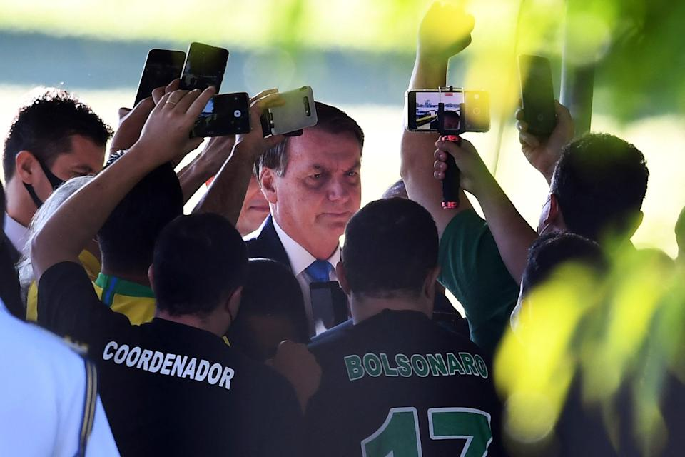 TOPSHOT - Brazilian President Jair Bolsonaro talks to supporters as he leaves the Alvorada Palace in Brasilia, on March 31, 2021. - President Jair Bolsonaro will replace all three commanders of Brazil's armed forces, his government said Tuesday, the latest upheaval in Brasilia as the far-right leader braces against mounting criticism over an explosion of Covid-19 deaths. (Photo by EVARISTO SA / AFP) (Photo by EVARISTO SA/AFP via Getty Images)