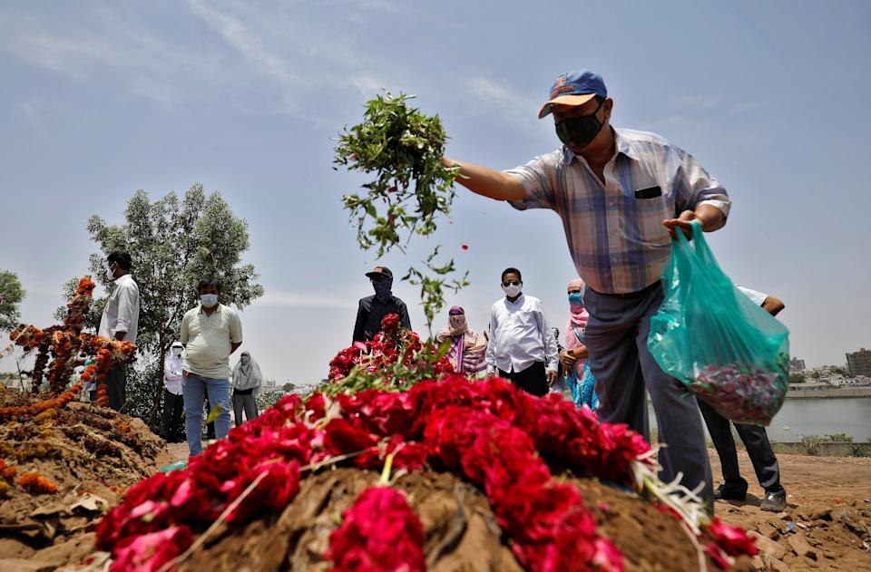 <p>A man scatters flower petals on the grave of a coronavirus victim</p> (Reuters)