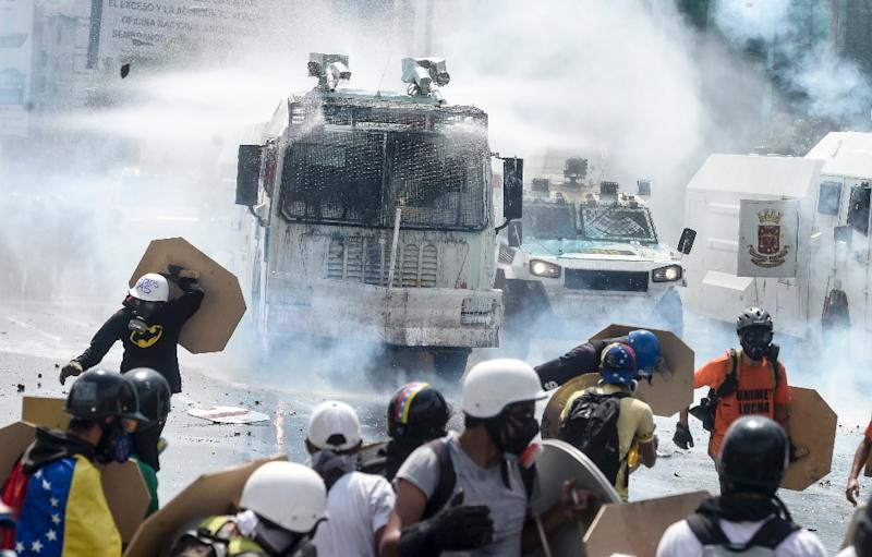 Opposition activists scatter as National Guard riot control vehicles charge during a protest against President Nicolas Maduro in Caracas, on May 10, 2017 (AFP Photo/JUAN BARRETO)