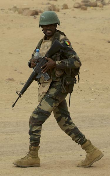 In this July 26, 2013 photo, a United Nations peacekeeper from Senegal patrols outside the mayor's office in Kidal, Mali. A bomb explosion killed several members of the U.N. peacekeeping mission in Mali in the troubled northern city of Kidal, a spokesman for the mission said Saturday, Dec. 14, 2013. (AP Photo/Rebecca Blackwell)