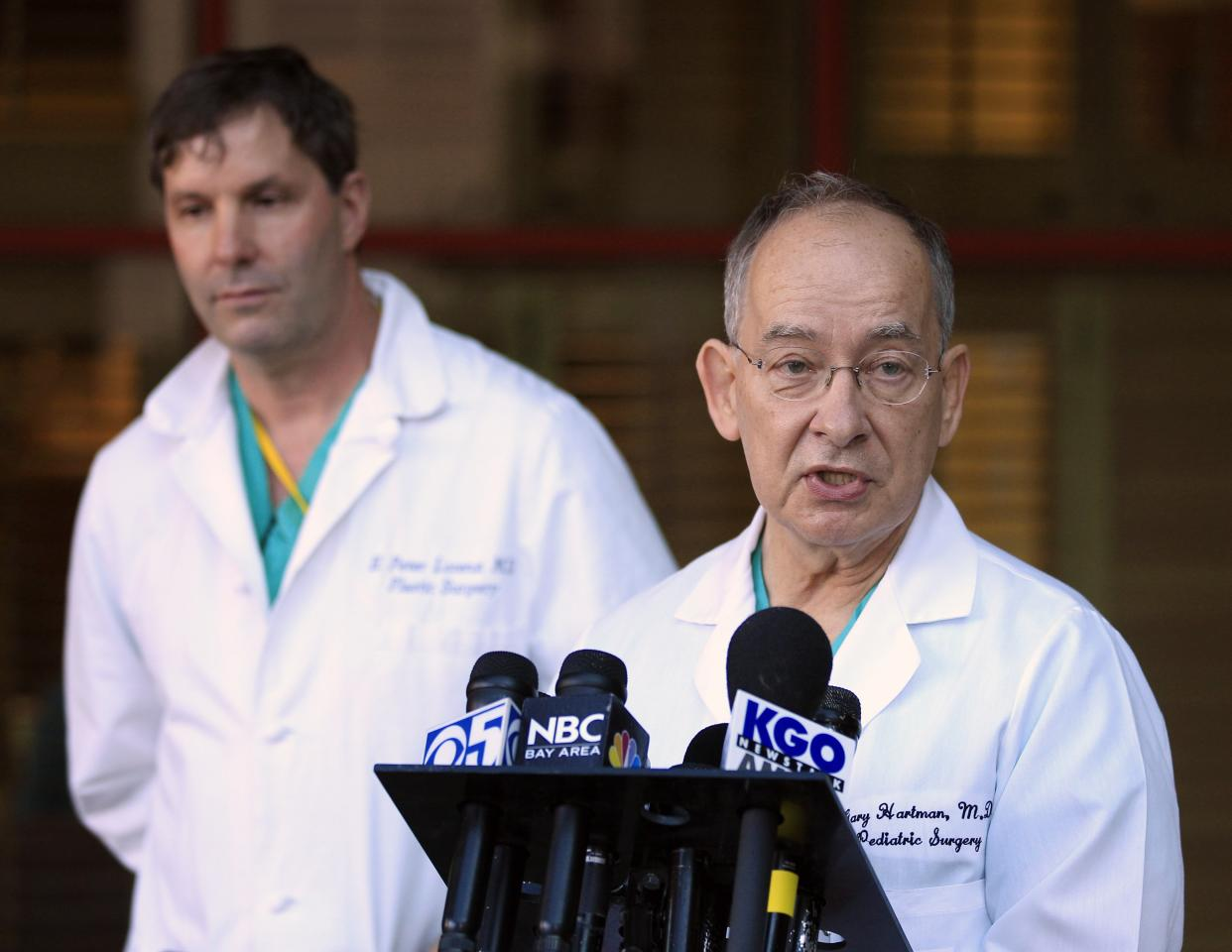 Pediatric surgeon Gary Hartman, at right, and plastic surgeon Peter Lorenz address the media following surgery on conjoined twins at the Lucile Packard Children's Hospital,Tuesday, Nov. 1, 2011 in Stanford, Calif. Twin 2-year-old girls Angelina and Angelica Sabuco underwent an expected nine hours of surgery by a team of more than 20 doctors and nurses at the Stanford hospital to gain their independence. The two sisters were born joined at the chest and abdomen and were separated Tuesday during a lengthy, complex procedure at the Stanford hospital. (AP Photo/Marcio Jose Sanchez)