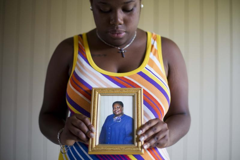 FILE - In this June 19, 2015 file photo, Najee Washington holds a photo of her grandmother Ethel Lance, one of the nine people killed in a shooting at Emanuel AME Church, by Dylan Roof, as she poses for a portrait outside her home in Charleston, S.C. The machete attack on a rabbi's home in Monsey, New York, during Hanukkah and the shooting of worshippers at a Texas church are refocusing attention on how vulnerable worshippers are during religious services. FBI hate crime statistics show there is reason for concern. (AP Photo/David Goldman, File)