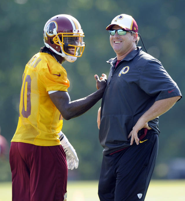 "FILE - In this June 17, 2014, file photo, Washington Redskins quarterback Robert Griffin III, left, laughs with head coach Jay Gruden during NFL football minicamp in Ashburn, Va. It didn't take long for Gruden to figure out Robert Griffin III. ""He's a perfectionist. He doesn't like negative publicity. He doesn't like negative plays to happen. He wants everything to be right,"" Gruden said. ""He wants everybody to love Robert, and that's not going to be the case at the quarterback position."" (AP Photo/Nick Wass, File)"