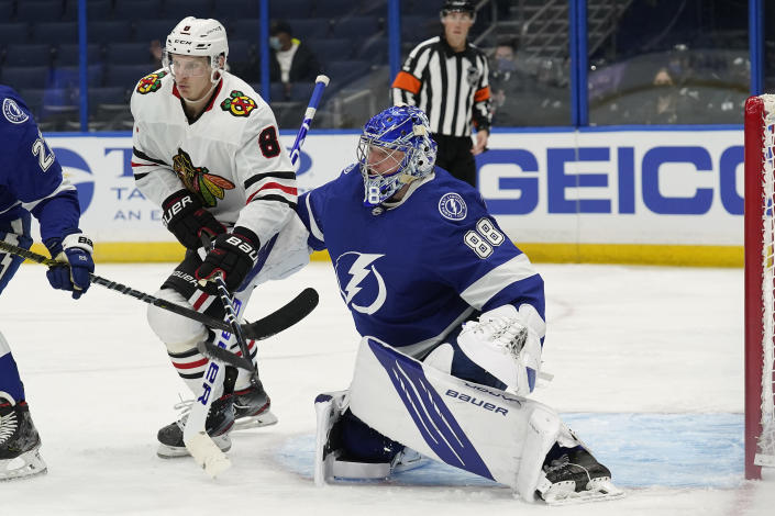 Tampa Bay Lightning goaltender Andrei Vasilevskiy (88) makes a save on a deflection by Chicago Blackhawks left wing Dominik Kubalik (8) during the third period of an NHL hockey game Friday, Jan. 15, 2021, in Tampa, Fla. (AP Photo/Chris O'Meara)