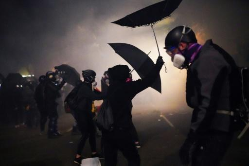 Protesters use umbrellas to block pepper balls while clashing with federal officers on July 22, 2020 in Portland, Oregon