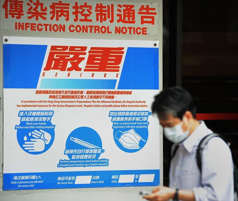 A man walks past precautionary signs permanently posted at a hospital on April 27, 2009 in Hong Kong