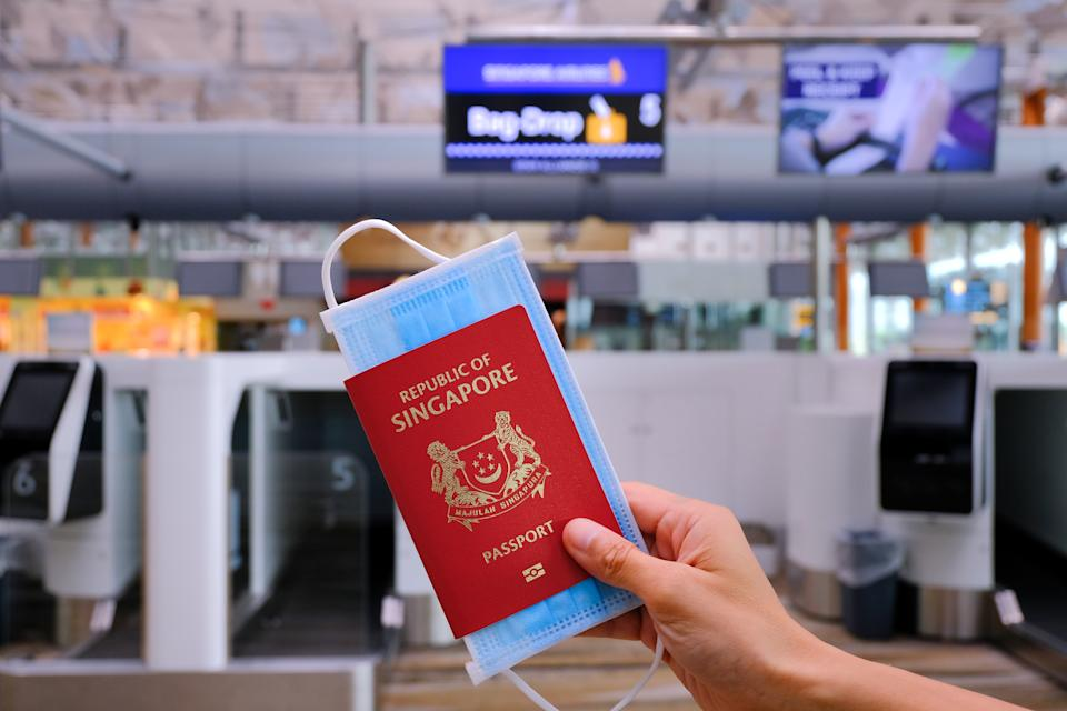 Airport check-in hall. Hand holding Singapore passport and face mask, at luggage check-in (bag drop). Travel concept. Reopening; coronavirus covid-19; travel restrictions.
