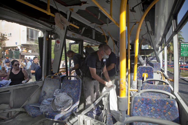 Israeli police officers examine a destroyed bus at the site of a bombing in Tel Aviv, Israel, Wednesday, Nov. 21, 2012. A bomb ripped through an Israeli bus near the nation's military headquarters in Tel Aviv on Wednesday, wounding several people, Israeli officials said. The blast came amid a weeklong Israeli offensive against Palestinian militants in Gaza.(AP Photo/Dan Balilty)