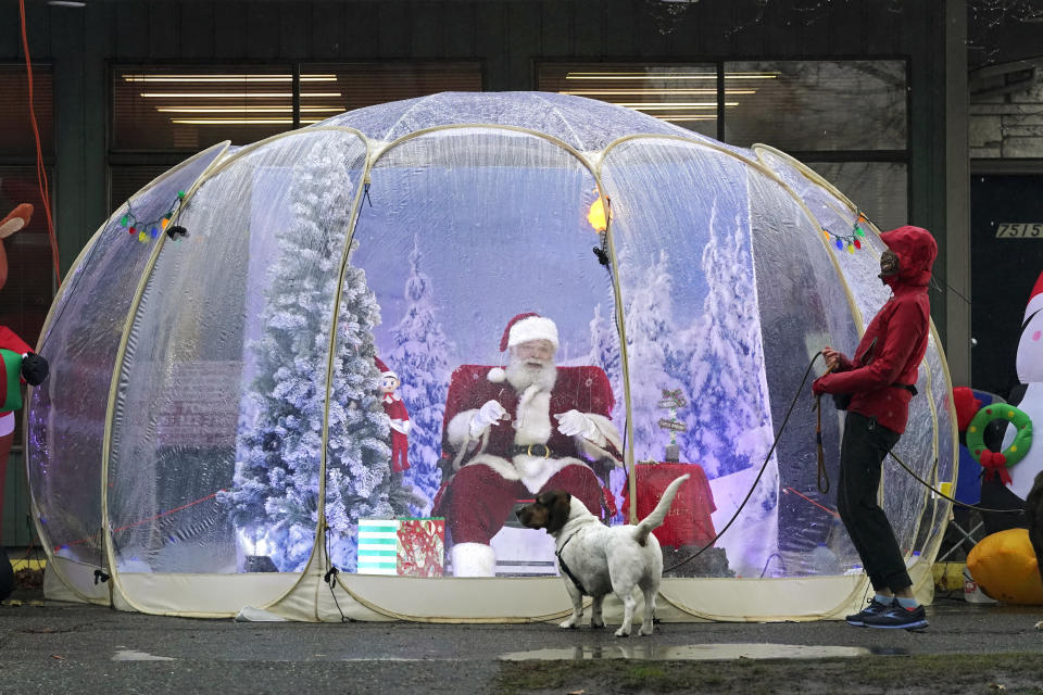 """Santa, portrayed by Dan Kemmis, laughs as he talks to Kristin Laidre as she walks her dog, Scooby, a Bassett Hound mix, as he sits inside a protective bubble in Seattle's Greenwood neighborhood on Dec. 8, 2020. Kemmis has been Santa in past years, but he started his daily appearances early this year and added his """"snow globe"""" tent due to the Coronavirus pandemic. In this socially distant holiday season, Santa Claus is still coming to towns (and shopping malls) across America but with a few 2020 rules in effect. (AP Photo/Ted S. Warren)"""