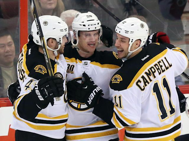 Boston Bruins' Daniel Paille (20) celebrates his goal against the Ottawa Senators with teammates Gregory Campbell (11) and Matt Bartkowski during the first period of an NHL hockey game in Ottawa, Ontario on Saturday, Dec. 28, 2013. (AP Photo/The Canadian Press, Fred Chartrand)